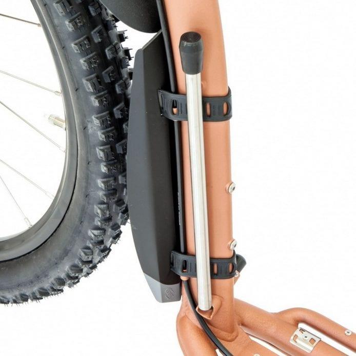 """Støtte for ettermontering på alle """"Mushing"""" modelene fra det Tjekkiske sparkesykkelmerket KOSTKA. (Følger med på Mushing Pro) Støtten er lett å ettermontere, er strikkbasert og er i oppslått possisjon ikke i veien når man skal sparke på sykkelen."""